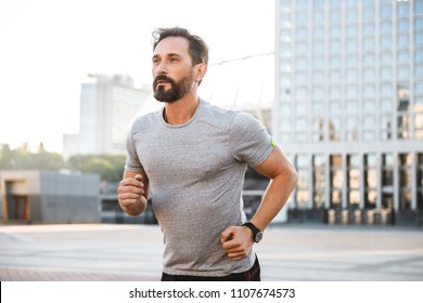 Image of handsome strong mature sportsman running at the street outdoors looking aside.