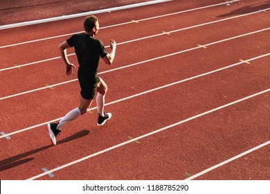 Image of handsome strong young sportsman running outdoors.