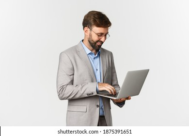 Image of handsome successful businessman working, standing in grey suit and using laptop, standing over white background