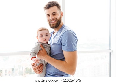 Image of handsome young bearded man holding his little son child in hands looking camera.