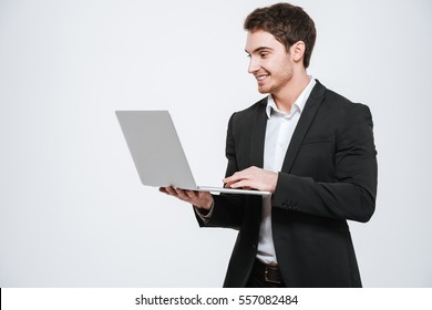 Image of handsome young caucasian businessman standing at studio. Isolated over white background. Look aside and holding laptop computer in hands.