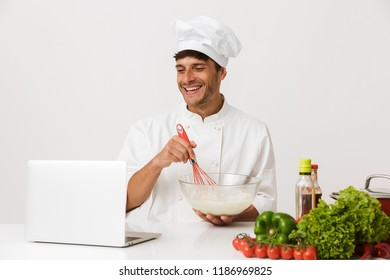 Image of handsome young chef man isolated over white wall background cooking using laptop computer.