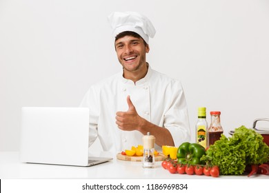 Image of handsome young chef man isolated over white wall background cooking make thumbs up gesture using laptop computer.