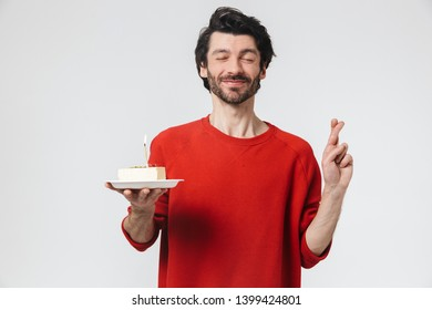 Image of a handsome young excited man posing isolated over white wall background holding birthday cake holidays showing hopeful gesture.