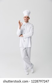 Image of handsome young man chef indoors isolated over white wall background.