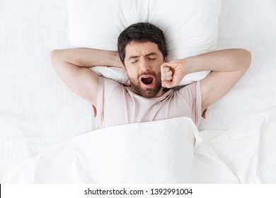 Image of a handsome young man in the morning yawning and stretching in bed.