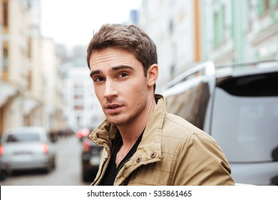 Image of handsome young man walking on the street and looking at camera.