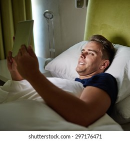 Image of a handsome young white man lying in his bed while surfing the web on his tablet