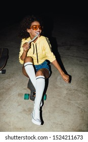Image of happy african american girl in streetwear eating long jelly candy and sitting on skateboard at night outdoors