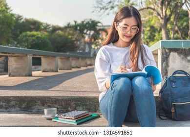Image of happy african young woman sitting outdoors in park writing notes in copybook listening music with earphones.
