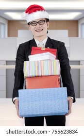 Image of happy Asian businessman holding stack of Christmas gifts while standing in the office
