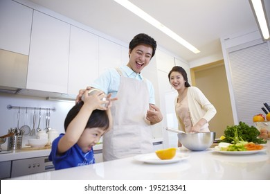 the image of a happy Asian family cooking