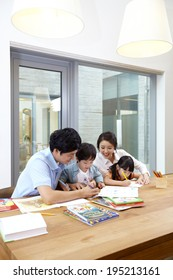 the image of a happy Asian family doing coloring