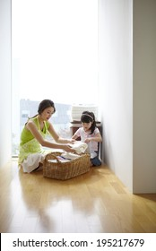 the image of a happy Asian family doing laundry