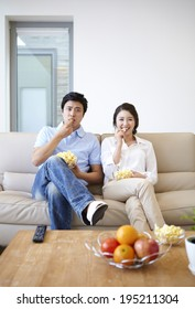the image of a happy Asian family eating popcorn