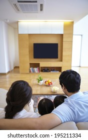 the image of a happy Asian family watching TV