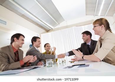 Image of happy business leaders handshaking at meeting