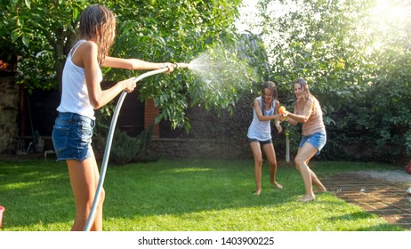 Image of happy cheerful family playing in backyard garden. People splashing water with water guns and garden hose.