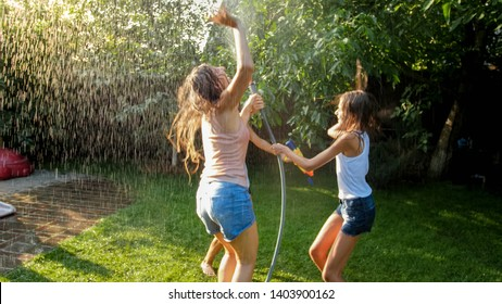Image of happy cheerful girls in wet clothes dancing and jumping under water garden hose. Family playing and having fun outdoors at summer