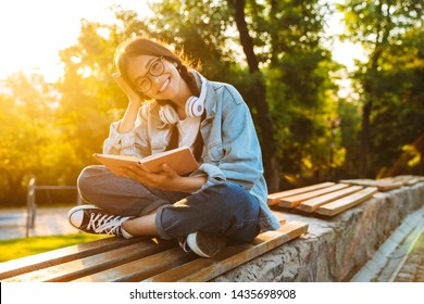 Image of a happy cheerful smiling young student girl wearing eyeglasses sitting outdoors in nature park listening music with headphones writing notes reading book.