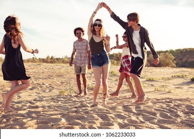 Image of happy cheerful young loving couples friends walking outdoors on the beach dancing.