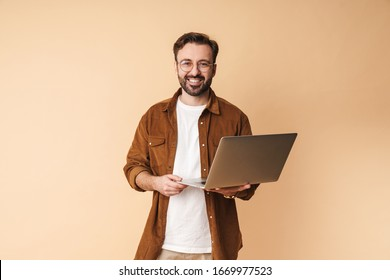 Image of a happy cheery optimistic young unshaved man isolated over beige wall background using laptop computer.