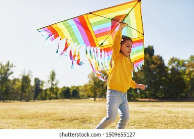 Image of a happy child little girl running with a big colorful kite on a sunny day outdoors. Cute kid playing and have fun outside with a kite in the park.