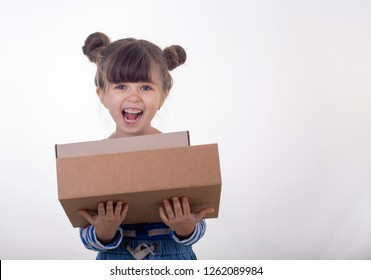 Image of a happy child standing with parcel post box isolated over white background. Internet purchases concept.