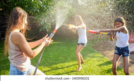 Image of happy children having water gun fight at house backyard garden. Family playing and having fun outdoors at summer
