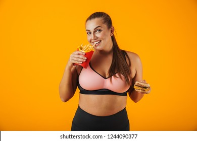 Image of happy chubby woman in tracksuit holding sandwich and french fries isolated over yellow background