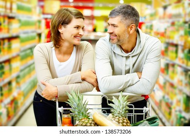 Image of happy couple with cart looking at one another in supermarket