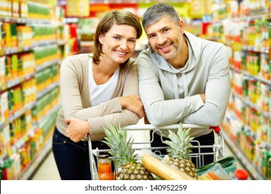 Image of happy couple with cart looking at camera in supermarket