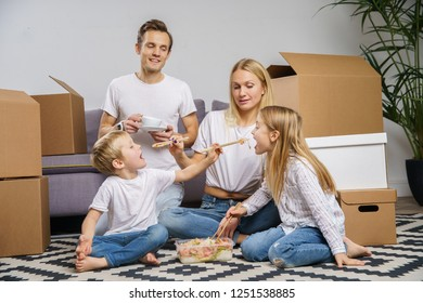 Image of happy couple with children eating rice with shrimps sitting on floor among cardboard boxes