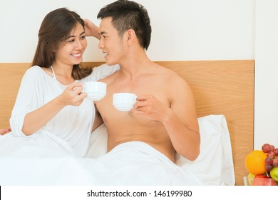 Image of a happy couple drinking morning coffee in bed