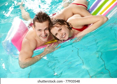 Image of happy couple looking at camera in swimming pool