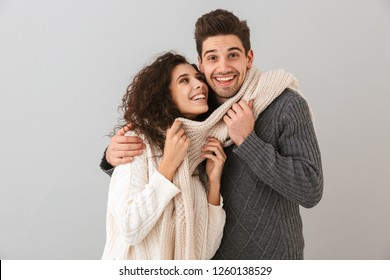 Image of happy couple man and woman smiling while hugging together isolated over gray background