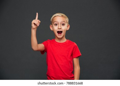 Image of happy cute little boy child standing isolated over grey background. Looking camera have an idea.
