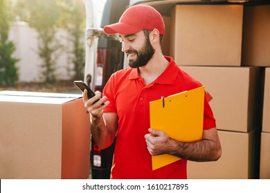 Image of happy delivery man holding clipboard and using cellphone while standing with parcel boxes outdoors
