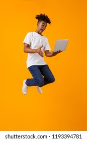 Image of happy excited young african man jumping isolated over yellow background using laptop computer.