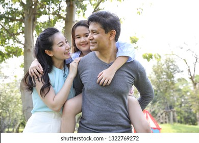 image of happy family, daughter riding behind father while parents smiling during summer time in the park