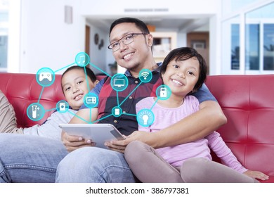 Image of happy father and his children holding digital tablet with smart house controllers system at home