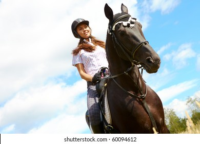 Image of happy female jockey on purebred horse outdoors