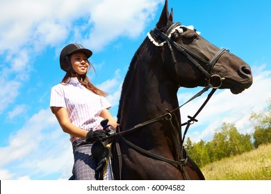 Image of happy female on purebred horse outdoors