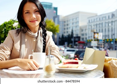 Image of happy female in open air cafe looking at camera in urban environment