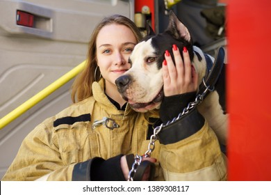 Image of happy firewoman with dog standing near fire truck