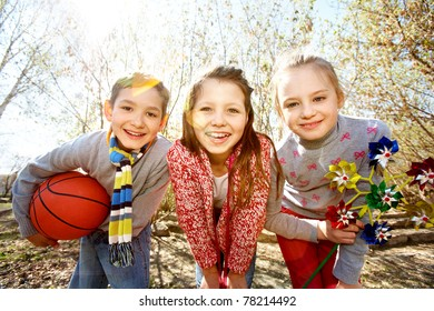 Image of happy friends with ball and toy looking at camera outdoors