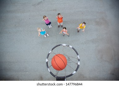 Image of happy friends playing basketball on sports ground