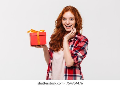 Image of Happy ginger woman in shirt holding gift box and looking at the camera over gray background