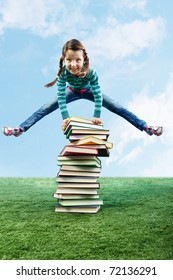 Image of happy girl jumping on the grass through stack of books