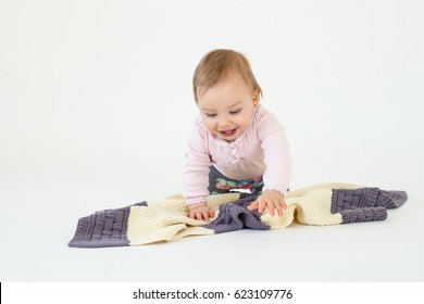 Image of happy girl sitting on floor with plaid isolated over white background. Looking aside.